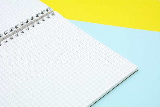 Livro de papel grade branca sobre fundo azul e amarelo Foto Premium