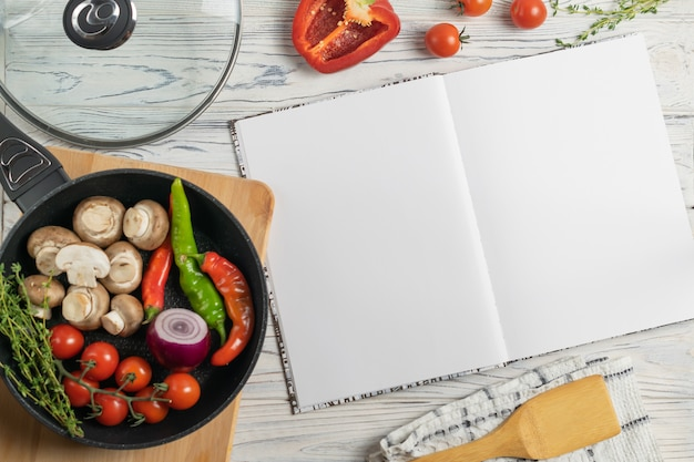 Livro de receitas com ingredientes orgânicos frescos na frigideira Foto Premium