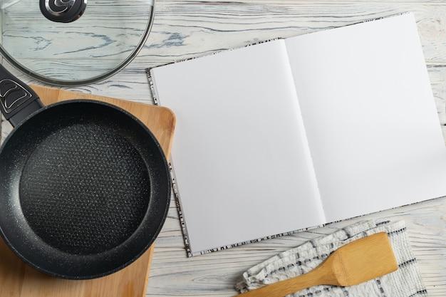 Livro de receitas e frigideira na mesa de madeira Foto Premium