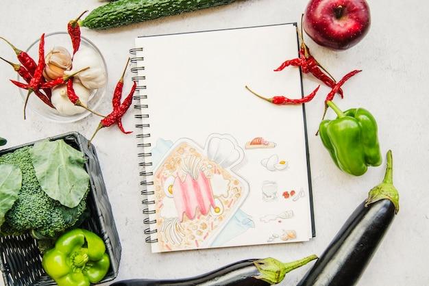Livro de receitas e ingrediente em fundo branco Foto gratuita