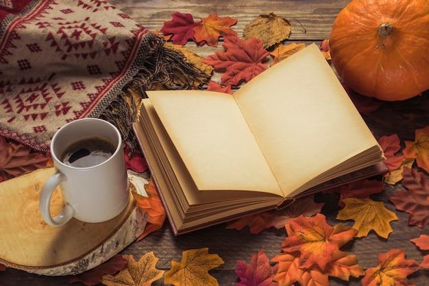 Livro e cobertor perto de bebida e abóbora Foto gratuita