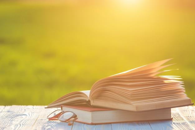 Livro e óculos na mesa de madeira com borrão abstrata e bokeh no nascer ou pôr do sol Foto Premium