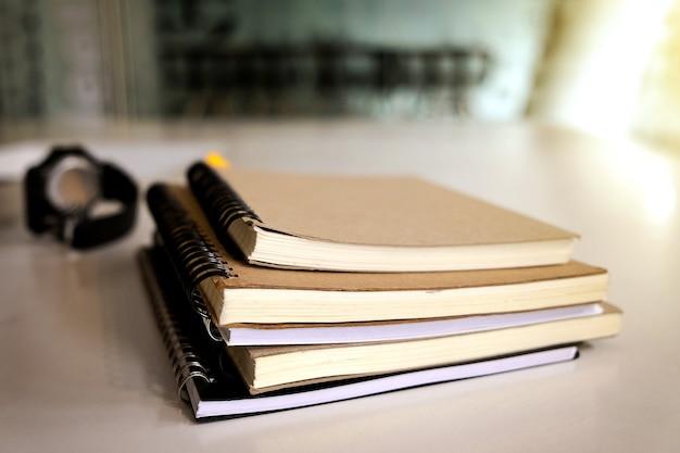 Livro e relógio de pulso na mesa de madeira com luz solar Foto Premium
