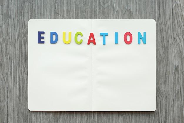 Livro em branco aberto com letras educação na tabela de madeira. Foto Premium