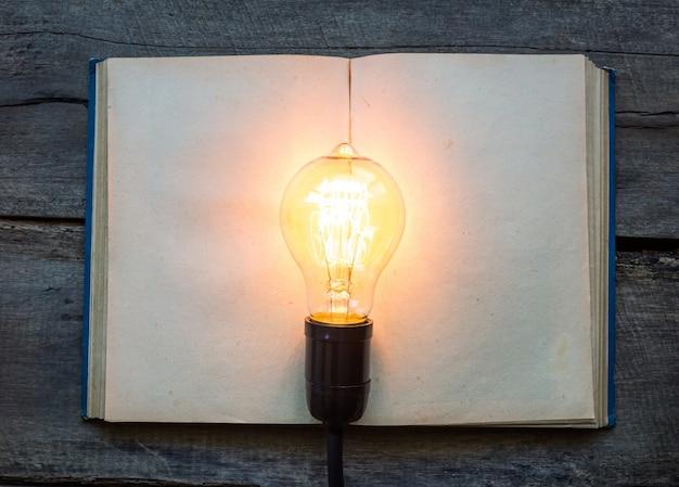 Livro em branco com uma lâmpada acesa no topo Foto gratuita