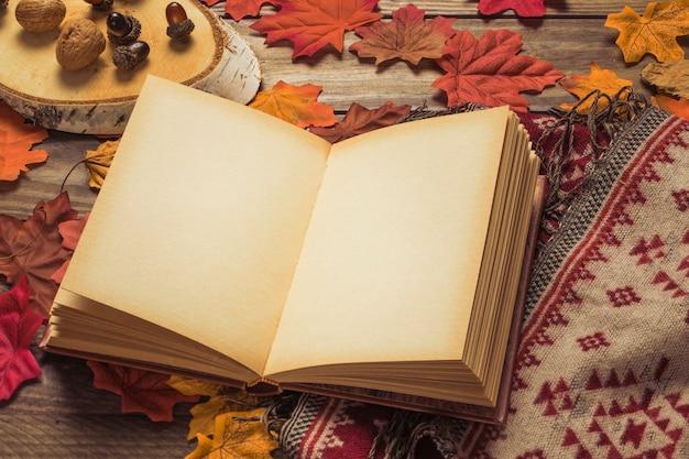 Livro em branco perto de nozes e cobertor em folhas Foto gratuita