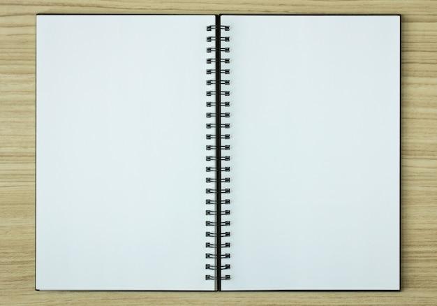 Livro espiral aberto em fundo de madeira Foto Premium
