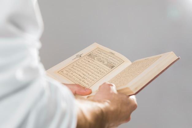 Livro muçulmano religioso sendo realizado nas mãos Foto gratuita