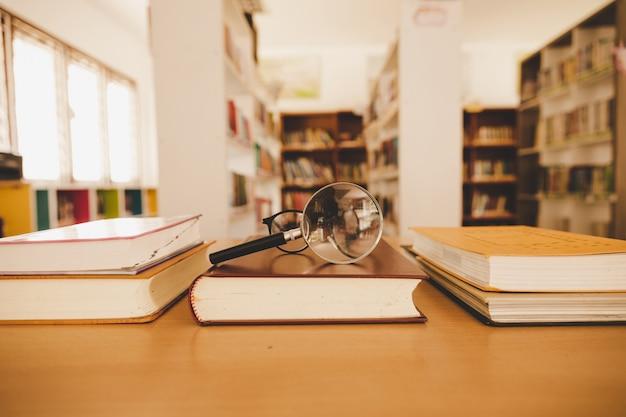 Livro na biblioteca com o velho livro aberto, pilha pilhas de arquivo de texto de literatura na mesa de leitura Foto gratuita