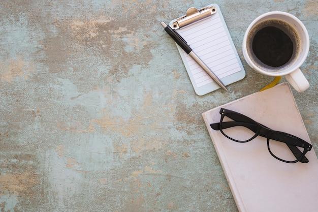 Livro; óculos; prancheta; caneta e xícara de café sobre fundo rústico Foto gratuita