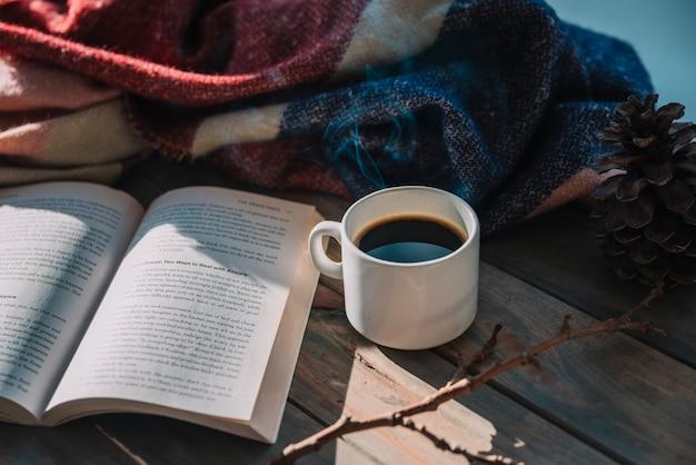 Livro perto de xícara e manta de lã na mesa Foto gratuita