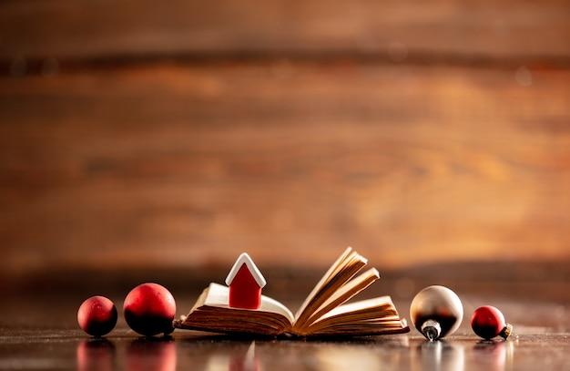 Livro velho com casa pequena e enfeites de natal na mesa de madeira Foto Premium