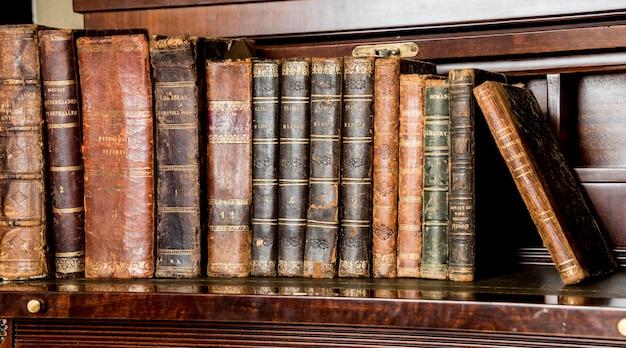 Livros antigos colocados em prateleiras de madeira Foto Premium