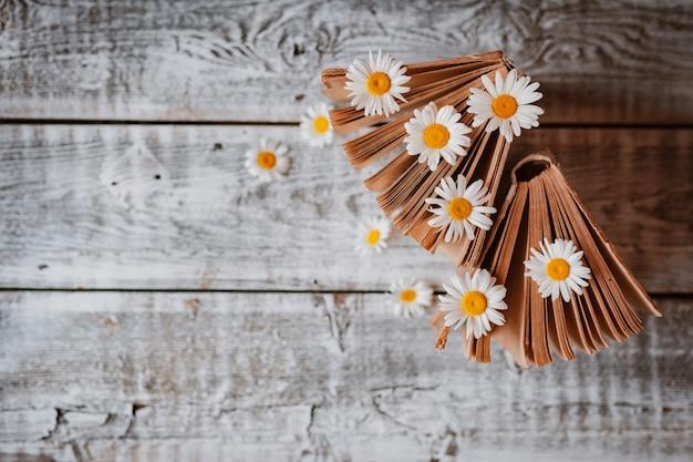 Livros antigos com flores de margaridas brancas. . espaço livre para texto Foto gratuita