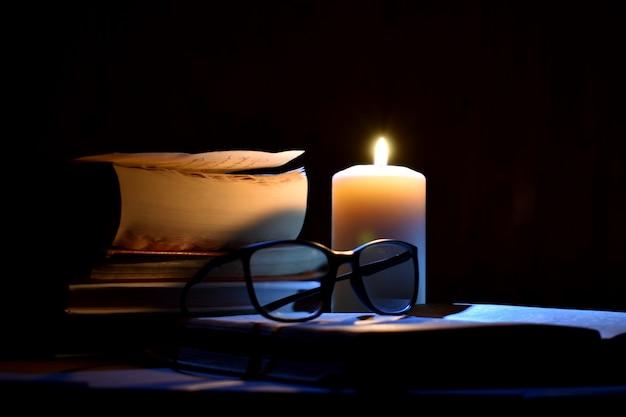 Livros antigos e velas acesas em um fundo preto. manuscritos antigos à luz de velas. Foto Premium