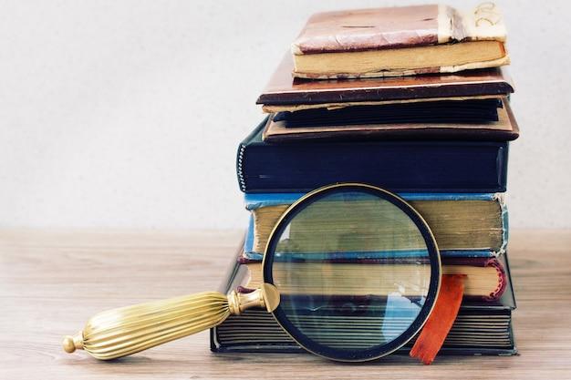 Livros antigos empilhados na mesa com antiquários Foto Premium