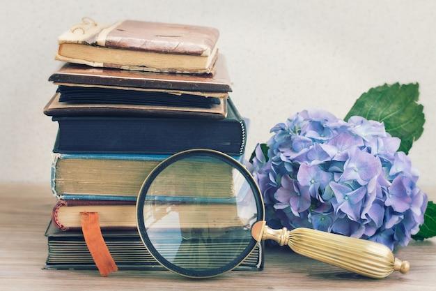 Livros antigos vintage com flores azuis de hortênsia e espelho empilhados na mesa Foto Premium