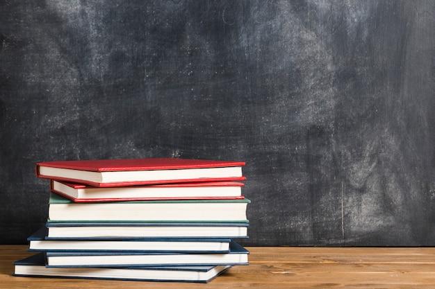 Livros coloridos frente do quadro-negro Foto Premium