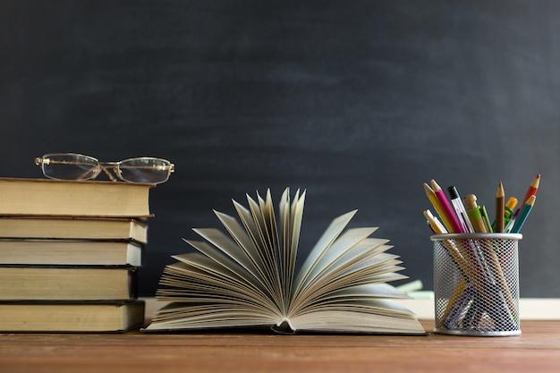 Livros de professor de óculos e um stand com lápis sobre a mesa, no fundo de um quadro negro com giz Foto Premium
