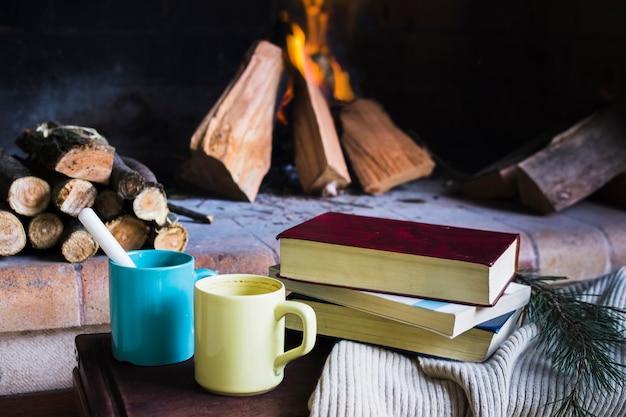 Livros e canecas perto da lareira Foto gratuita
