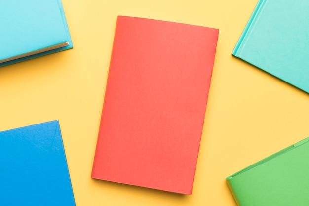 Livros fechados, dispostos na mesa amarela Foto gratuita