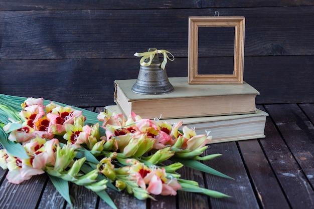 Livros, gladiulos, uma moldura para uma foto e um velho sino Foto Premium
