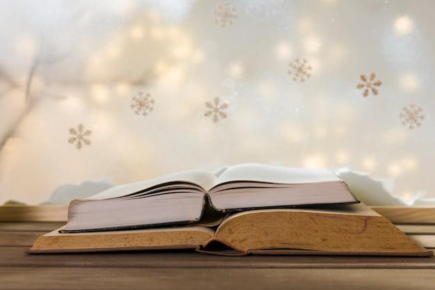 Livros na mesa de madeira perto do banco de neve, flocos de neve e luzes de fada Foto gratuita