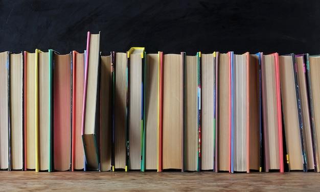 Livros nas capas coloridas na prateleira no fundo de uma lousa de escola. Foto Premium