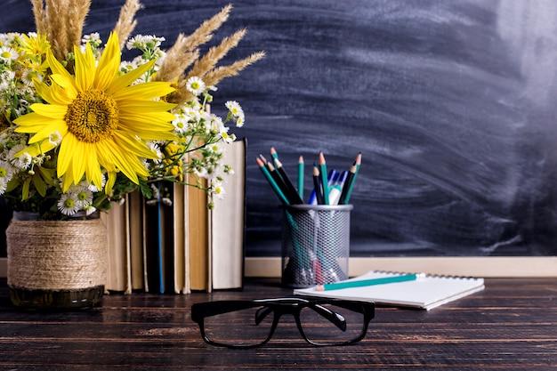 Livros, óculos, marcadores e um buquê de flores em um vaso branco Foto Premium