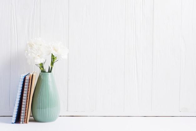 Livros perto das flores frescas no vaso contra papel de parede pintado de madeira branca Foto gratuita
