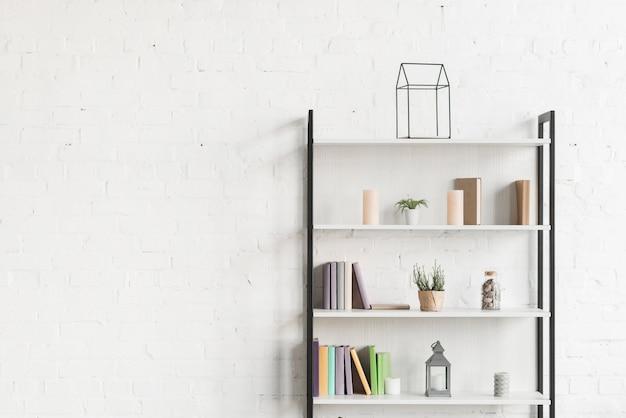 Livros, show de plantas e velas nas prateleiras da sala de estar Foto gratuita