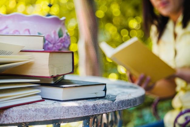 Livros sobre mesa e leitura de mulher Foto gratuita