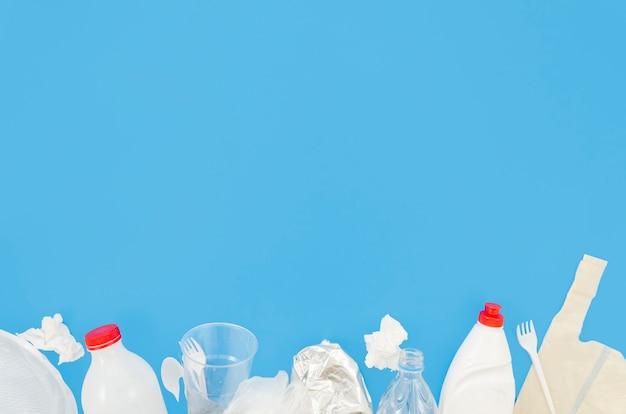 Lixo de plástico e papel amassado, dispostas na parte inferior do fundo azul Foto gratuita