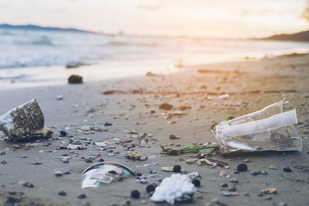 Lixo na areia da praia, mostrando o problema de poluição ambiental Foto gratuita