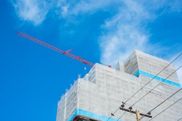 Local de construção de edifício alto arranha-céus com guindaste no céu azul Foto Premium