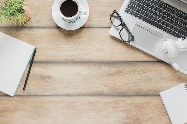 Local de trabalho com artigos de papelaria, dispositivos eletrônicos e xícara de café na mesa de madeira Foto gratuita