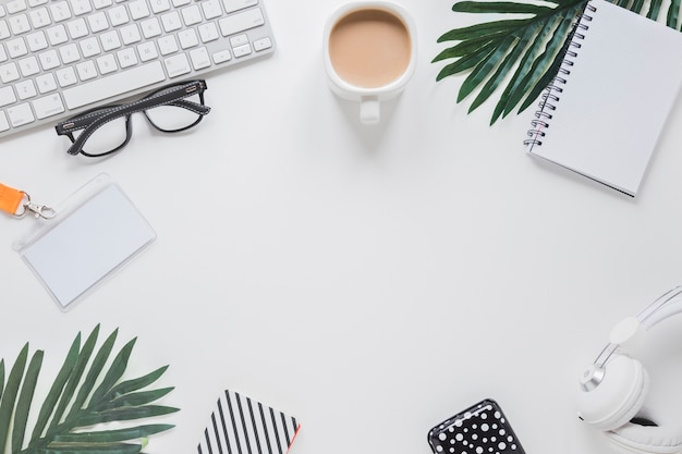 Local de trabalho com gadgets, xícara de café e copos perto de palmeiras Foto gratuita
