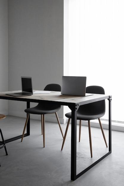 Local de trabalho com laptop e cadeiras Foto Premium