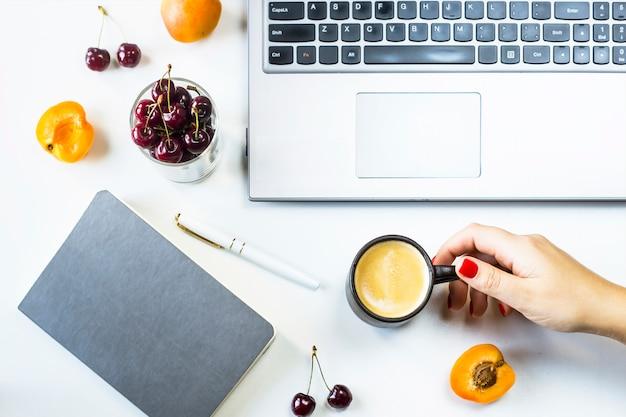 Local de trabalho com laptop e notebook em uma mesa branca com frutas e frutas lanche Foto Premium