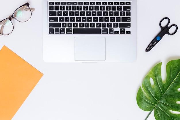 Local de trabalho com laptop e tesoura Foto gratuita