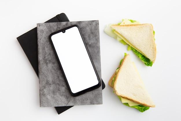 Local de trabalho com prato de deliciosos sanduíches Foto gratuita