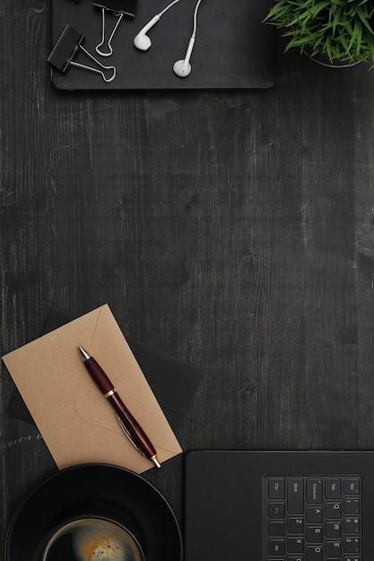 Local de trabalho com smartphone, notebook, mesa preta. vista do topo Foto gratuita