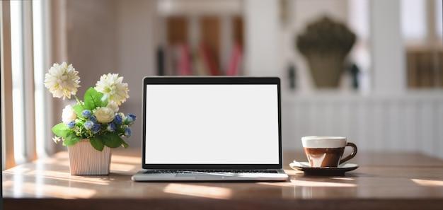 Local de trabalho confortável com mock-se computador portátil, xícara de café e pote de árvore na mesa de madeira Foto Premium
