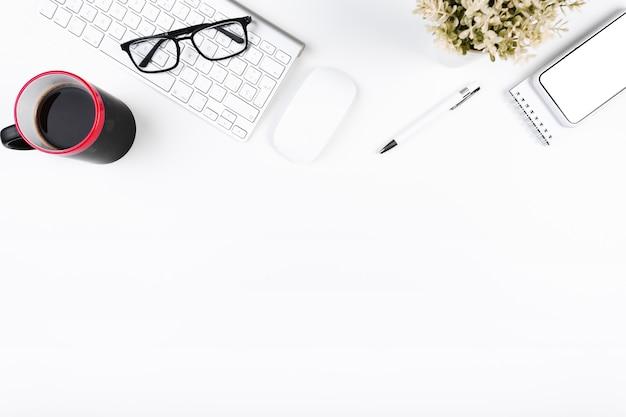 Local de trabalho de escritório acolhedor com teclado e copo Foto gratuita