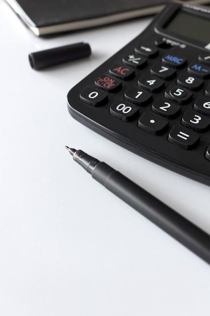 Local de trabalho do escritório com espaço de texto, livro preto e calculadora na mesa branca Foto Premium