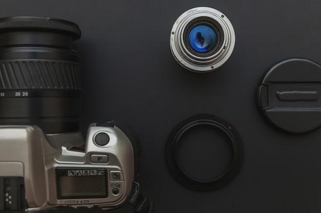 Local de trabalho do fotógrafo com sistema de câmera dslr e lente no fundo da mesa de preto escuro. conceito de fotografia de viagens passatempo. vista plana leiga cópia espaço. Foto Premium
