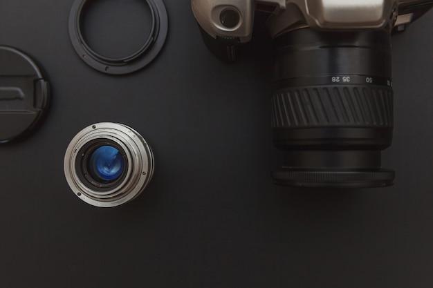 Local de trabalho do fotógrafo com sistema de câmera dslr e lente no fundo da mesa de preto escuro Foto Premium