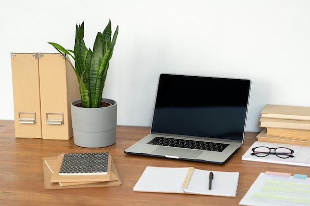 Local de trabalho do gerente de escritório ou aluno com laptop, planta em vaso, cadernos, livros e outros suprimentos na mesa Foto Premium
