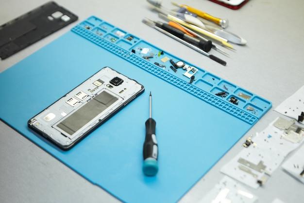 Local de trabalho do reparador com telefone celular e ferramentas especiais na mesa Foto gratuita