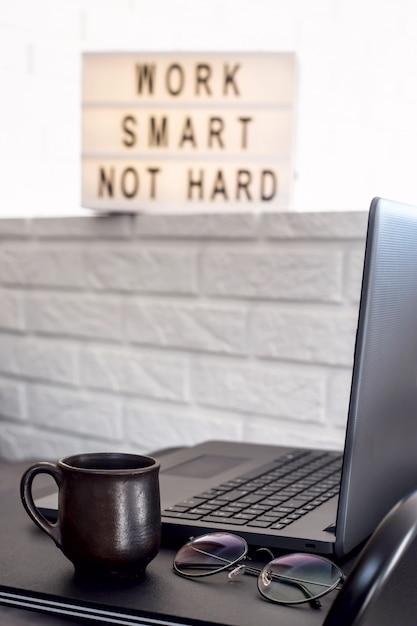 Local de trabalho em casa de um freelancer em uma mesa preta elegante perto do sofá e a parede de tijolo Foto Premium